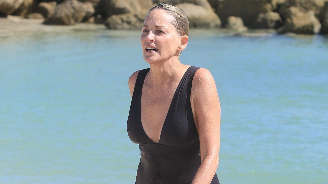 f5d19cde98 Sharon Stone Turns Heads in Plunging Black Swimsuit While Playing in the  Waves
